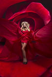 La bella giovane signora nei supporti rossi del vestito sul fiore è aumentato Fotografie Stock Libere da Diritti