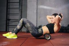 La bella giovane sportiva caucasica della donna utilizza un massaggiatore del rullo della schiuma per rilassamento, allungando i  fotografie stock libere da diritti