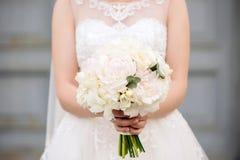 La bella giovane sposa tiene il mazzo di nozze delle peonie pastelli dei toni di beige in mani con il manicure francese sul blure Fotografia Stock