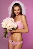 La bella giovane sposa in velo bianco ed impallidisce la biancheria rosa del pizzo con il mazzo delle peonie a disposizione Fotografia Stock