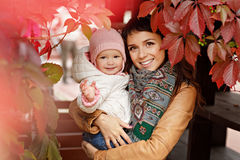 La bella mamma castana molto affascinante con marrone osserva tenendo una l fotografia stock