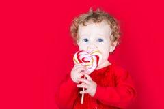 La bella neonata riccia che mangia un cuore ha modellato la caramella sul BAC rosso Fotografia Stock