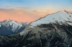 La bella neve ha ricoperto le montagne contro il cielo crepuscolare a Banf immagini stock