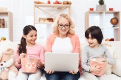 La bella nonna anziana esamina il computer portatile con i suoi piccoli nipoti immagine stock