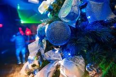 La bella palla sui rami dell'albero di Natale con il blu ha illuminato ed offuscato il fondo Immagine Stock