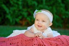 La bella piccola neonata sta trovandosi su una coperta del plaid Fotografia Stock