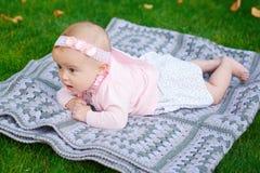 La bella piccola neonata sta trovandosi su una coperta del plaid Immagine Stock
