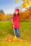 La bella piccola ragazza lavora con il rastrello giallo Fotografie Stock
