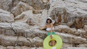 La bella ragazza abbronzata in un costume da bagno ed in un cappello posa su una macchina fotografica vicino ad una scogliera con stock footage
