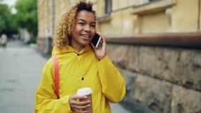La bella ragazza afroamericana sta parlando sul telefono cellulare e tenendo porti via il caffè che cammina nella città lungo la  stock footage