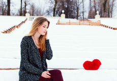 La bella ragazza alla moda si siede nell'inverno su un banco Fotografie Stock Libere da Diritti