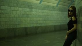 La bella ragazza alla moda in vetri sta in un sottopassaggio pedonale vicino alla parete stock footage