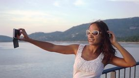 La bella ragazza allegra castana in occhiali da sole prende le foto del tramonto sulla macchina fotografica del telefono cellular archivi video