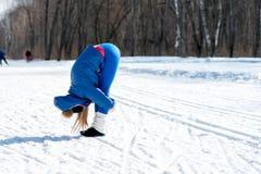 La bella ragazza allunga ancora su un campo sportivo nell'inverno Immagini Stock
