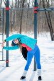 La bella ragazza allunga ancora su un campo sportivo nell'inverno Immagine Stock