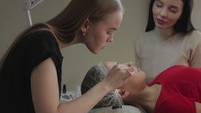 La bella ragazza ammira i cigli, che la sua accumulazione in un salone di bellezza stock footage
