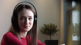 La bella ragazza ascolta musica in caffè archivi video