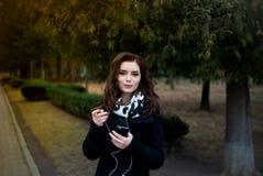 La bella ragazza ascolta musica nel parco Fotografia Stock Libera da Diritti