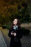 La bella ragazza ascolta musica nel parco Immagine Stock