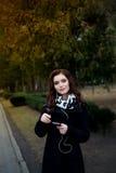 La bella ragazza ascolta musica nel parco Immagini Stock Libere da Diritti