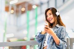 La bella ragazza asiatica ascolta musica facendo uso del sorriso della cuffia e dello smartphone allo spazio della copia, all'hob immagine stock libera da diritti