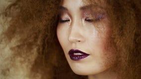 La bella ragazza asiatica con un aspetto luminoso ha esaminato la macchina fotografica stock footage