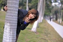 La bella ragazza asiatica pura fa una pausa un albero Immagine Stock