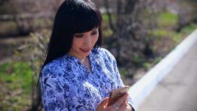 La bella ragazza asiatica si siede in un parco su un banco e scrive un messaggio su uno smartphone archivi video