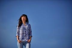 La bella ragazza asiatica sta in blue jeans contro il cielo blu Fotografia Stock