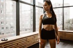 La bella ragazza atletica con capelli marroni si è vestita negli sport neri superiori e mette i supporti in cortocircuito nella p fotografia stock libera da diritti