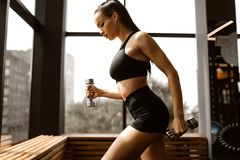La bella ragazza atletica con capelli marroni vestiti negli sport neri superiori e mette tiene le teste di legno nella palestra fotografie stock libere da diritti