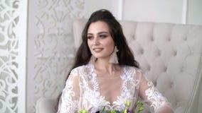 La bella ragazza attraente sta sedendosi in una sedia Giovane donna in un vestito bianco dal pizzo archivi video