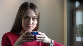 La bella ragazza beve il caffè e sorride stock footage