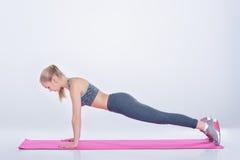 La bella ragazza bionda in abiti sportivi fa gli esercizi sulla stuoia di forma fisica su fondo grigio Immagini Stock Libere da Diritti
