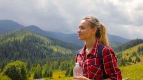 La bella ragazza bionda beve l'acqua nelle montagne stock footage
