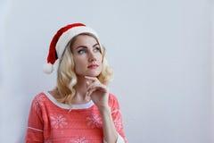 La bella ragazza bionda in cappello di natale pensa a natale fotografia stock