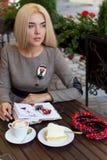 La bella ragazza bionda che si siede al caffè con gli impianti del dolce e della tazza di caffè e disegna gli schizzi in un taccu Immagini Stock