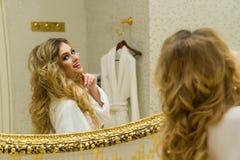 La bella ragazza bionda corregge i suoi capelli e lo sguardo nello specchio nel suo bagno La giovane donna di bellezza corregge i Fotografie Stock