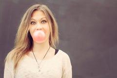 La bella ragazza bionda gonfia una bolla rossa da gomma da masticare Fine in su esterno Fotografia Stock Libera da Diritti