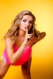 La bella ragazza bionda mostra il segreto di gesto Fotografia Stock