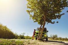 La bella ragazza in breve stare accanto al camper classico del vecchio temporizzatore sotto l'albero un giorno di estate luminoso fotografie stock libere da diritti