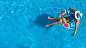 La bella ragazza in cappello nella vista aerea del fuco della piscina da sopra, donna si rilassa e nuota sulla ciambella gonfiabi immagini stock libere da diritti
