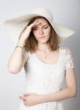La bella ragazza in cappello a tesa larga che posa ed esprime le emozioni differenti emicrania, tristezza, affaticamento Fotografie Stock Libere da Diritti