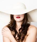 La bella ragazza in cappello a tesa larga che posa ed esprime le emozioni differenti emicrania, tristezza, affaticamento Fotografia Stock