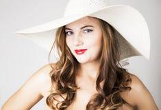 La bella ragazza in cappello a tesa larga che posa ed esprime le emozioni differenti emicrania, tristezza, affaticamento Immagine Stock