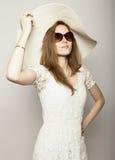 La bella ragazza in cappello a tesa larga ed occhiali da sole che posano ed esprime le emozioni differenti Immagini Stock