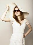 La bella ragazza in cappello a tesa larga ed occhiali da sole che posano ed esprime le emozioni differenti Fotografie Stock Libere da Diritti