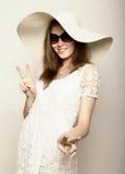 La bella ragazza in cappello a tesa larga ed occhiali da sole che posano ed esprime le emozioni differenti Fotografia Stock