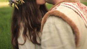La bella ragazza castana in camicia ucraina tradizionale con la corona del fiore bacia il suo ragazzo alla molla verde archivi video