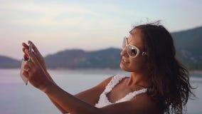 La bella ragazza castana in occhiali da sole prende le foto del tramonto sulla macchina fotografica del telefono cellulare Movime video d archivio